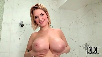 Curvy cutie rubs her big tits in the shower